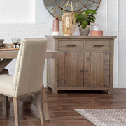 Lifestyle photograph of Farringdon reclaimed wood medium sideboard in tree-quarter profile. Image shows to draw with cupboard beneath, styled with dining table and terracotta pottery.