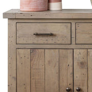 Cut-out photograph on white background of Farringdon reclaimed wood medium sideboard. Image shows close-up of top drawer of unit with cupboard beneath.
