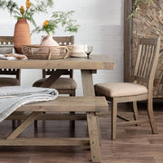 Lifestyle photograph of Farringdon reclaimed wood extendable trestle table. Image styled with matching reclaimed wood bench and dining chair, terracotta plant pots and cabinet in the background.