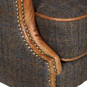 Close up image of tweed fabric and leather detailings, with brass studs