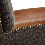 Image shows brass stud detailing of blue grey tweed with tan arms