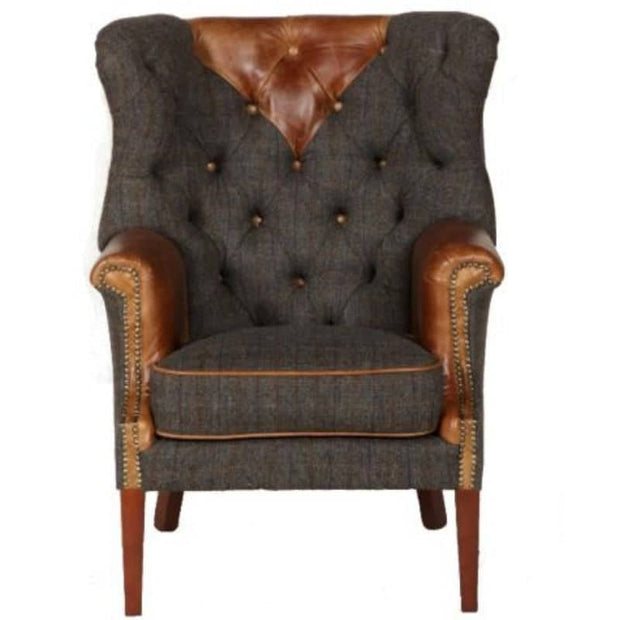 Front profile of grey blue tweed armchair with tan leather and grass stud details