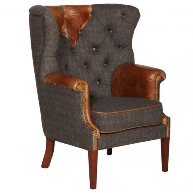 CUt out image of tweed wingback armchair with tan leather detailing and brass studs