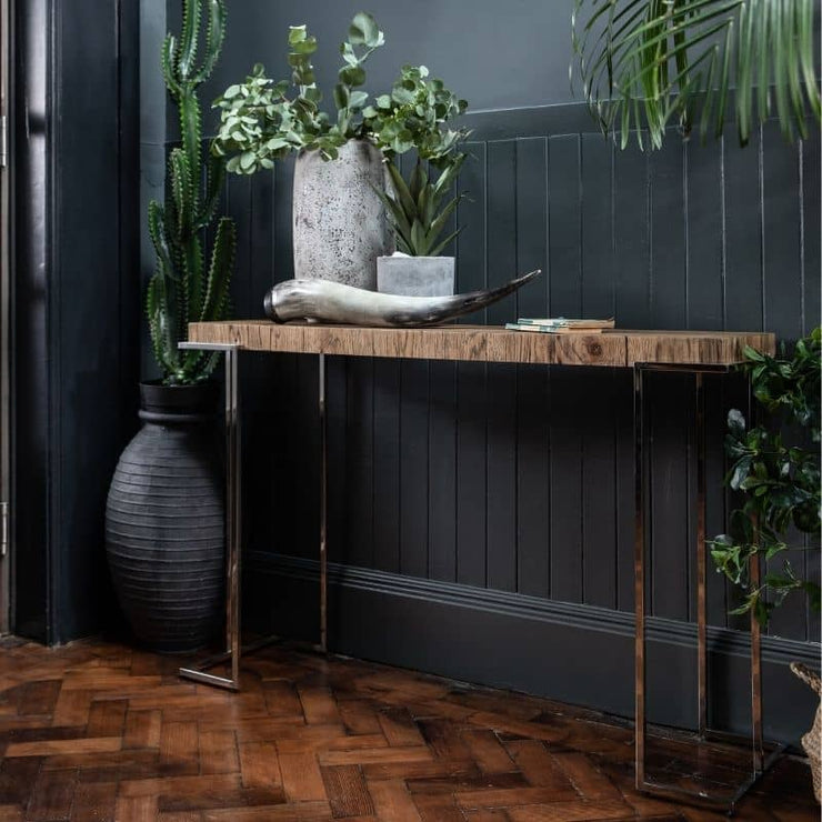 The Knightsbridge Reclaimed Oak Console Table stands in a hallway surrounded by green plants.