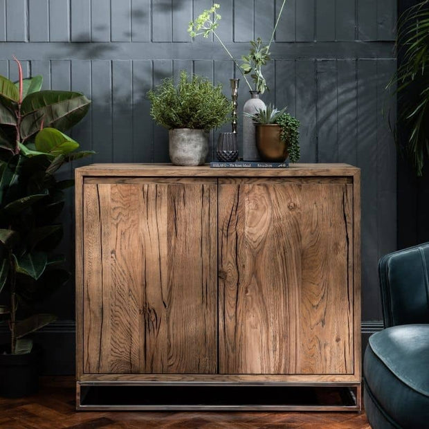 The Knightsbridge Small Reclaimed Oak Sideboard against a dark panelled wall with plants.