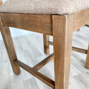 Close up of fabric and wooden leg of standford dining chair