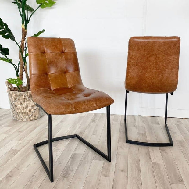 Pair of standford leather dining chairs with plant in background