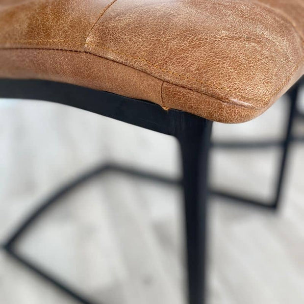 Close up of leather and sticking near leg of standford leather dining chair