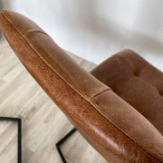 Close up of leather and stitching on top of leather dining chair