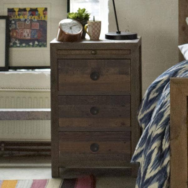A reclaimed wood bedside table with a dark finish and decorative items