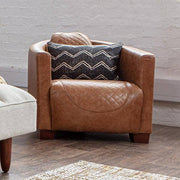 A tan brown leather armchair with a geometric pillow