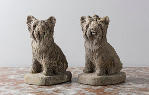 A pair of reconstituted stone seated French terriers