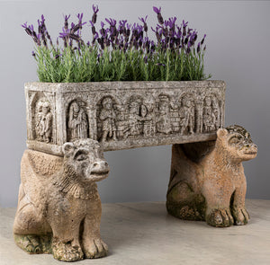 An unusual carved composite stone medieval style planter with carved stone mythical animal supports, French 18/19th Century