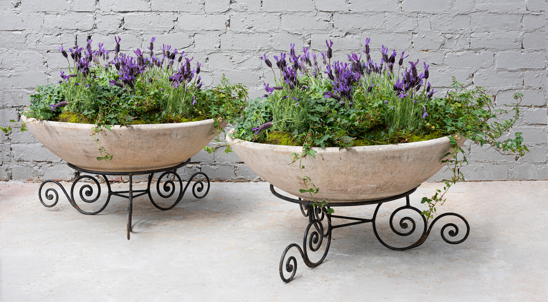 A pair of circular vintage jardinieres on decorative black iron bases, French Circa 1950