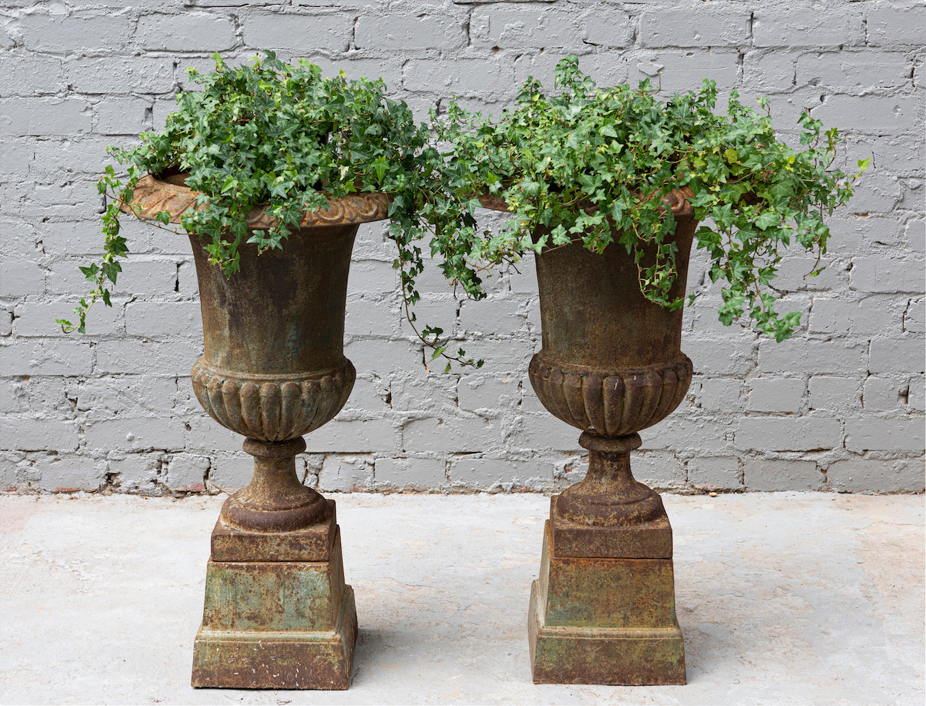 A pair of large cast-iron Classical urns on stands, French 19th Century