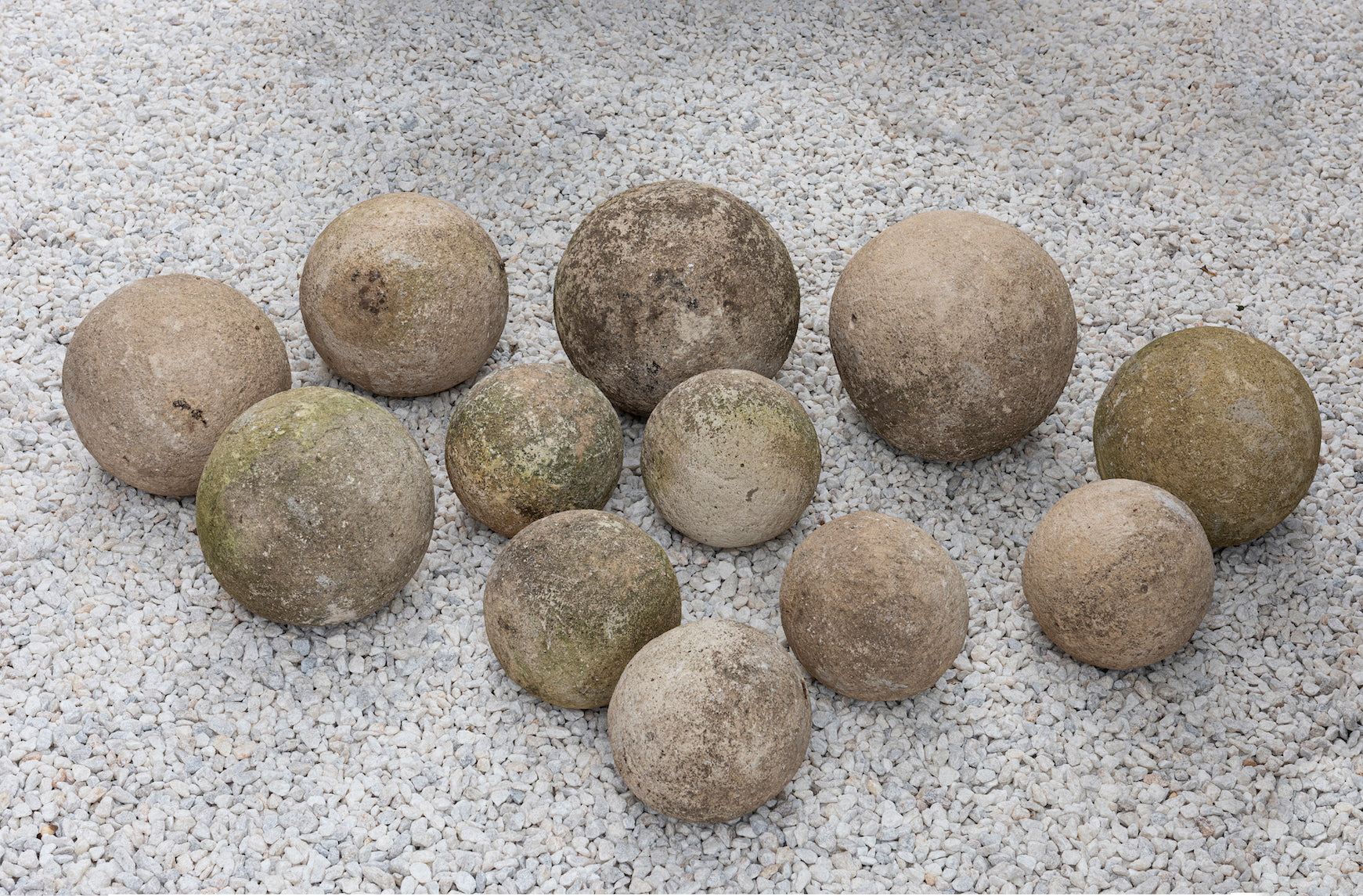 Five pairs of varying sized carved sandstone garden spheres, French 19th Century