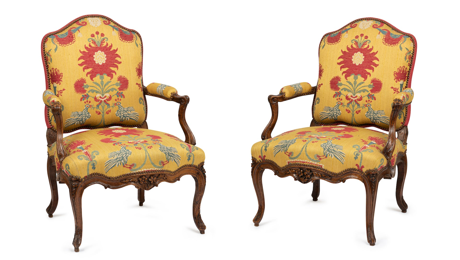 An exceptional pair of Louis XV period carved walnut fauteuils, French 18th Century