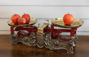 An imposing set of brass, red painted and ornate steel butchers scales, French 19th Century