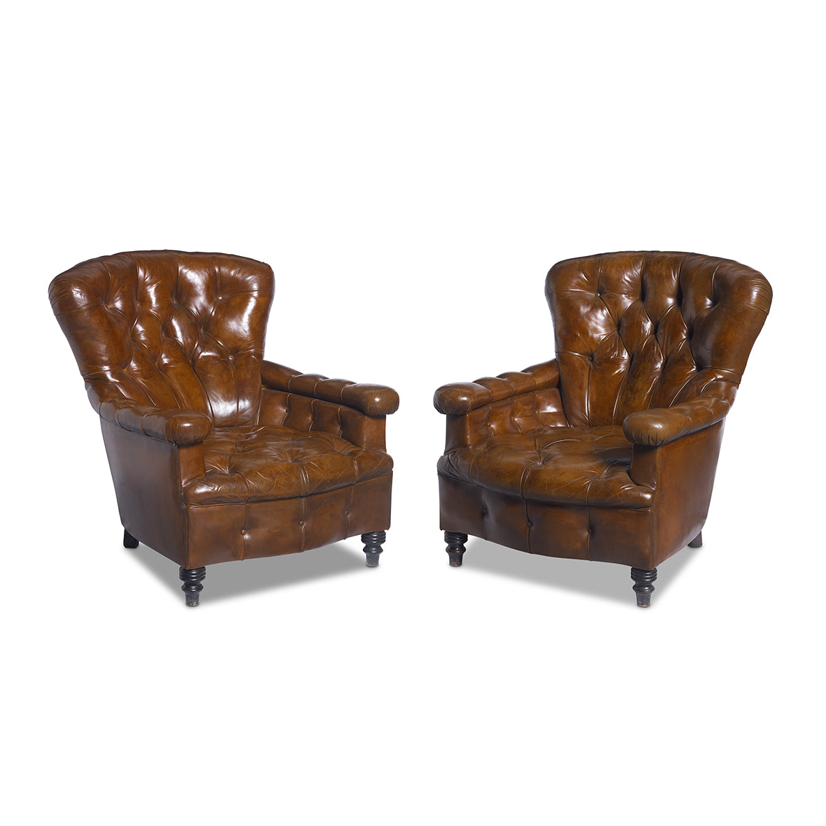 An outstanding pair of buttoned tan leather armchairs, French, 19th Century