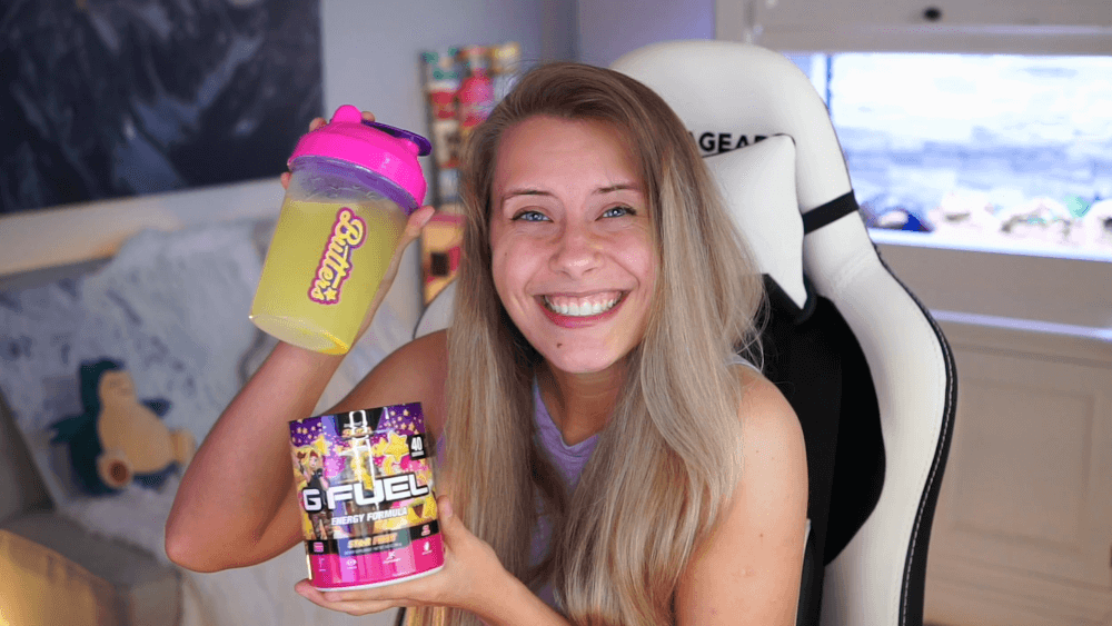 NoisyButters is holding her G FUEL Star Fruit shaker cup and tub while smiling and sitting in a gaming chair.