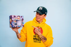 Logic is wearing a yellow hoodie and No Pressure hat, and holding a limited-edition G FUEL Bobby Boysenberry Collectors Box, which includes one 40-serving tub and one 16 oz Bobby Boy shaker cup.