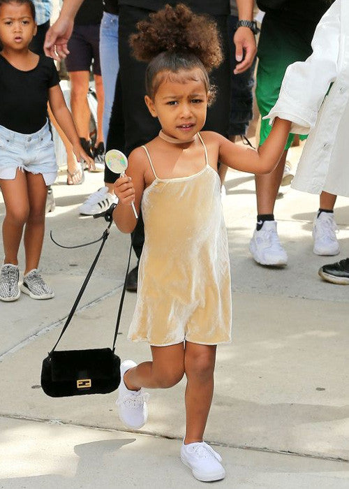 north west in a gold slip dress
