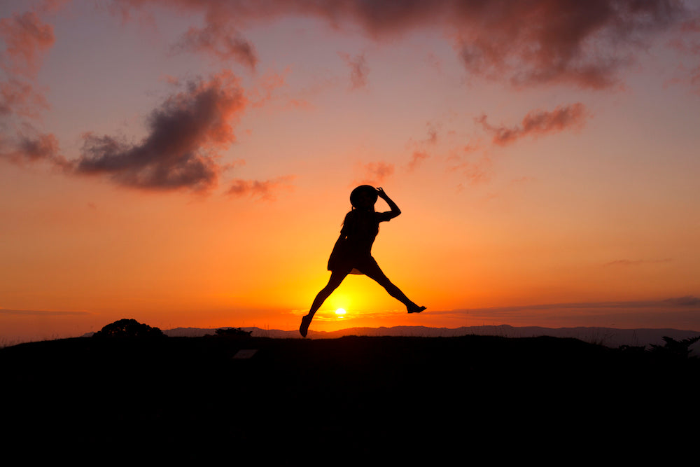 girl jumping sunset LOTUSWEI flower essences