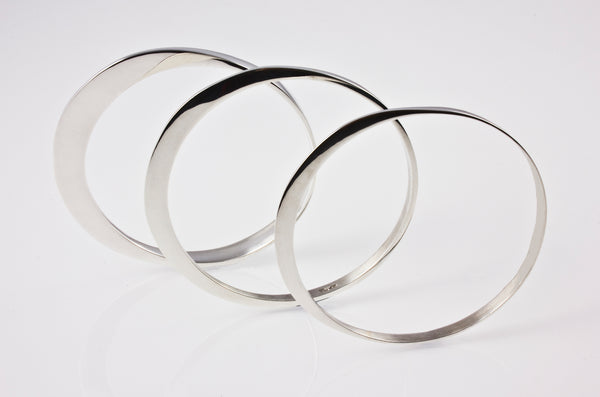 Circle of Dreams Silver Bangles. Material: Sterling silver Measurements: Small - 64mm inside diameter.                           Medium - 66mm inside diameter.                           Large - 68mm inside diameter. Approximate Weight: DL11A/s, 11grams; DL11B/s, 24grams; DL11C/s, 38grams. Design Year: 1991