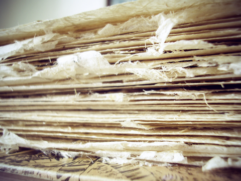 Stack of paper with frayed edges.