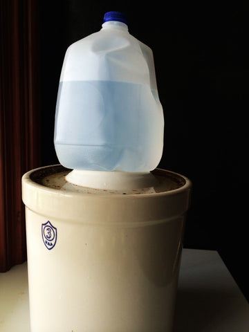 A gallon jug of water on top of a crock.