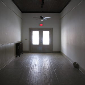 An empty room with windows on the front wall.