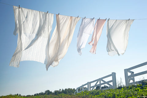 Cotton sheets hanging on a clothesline.