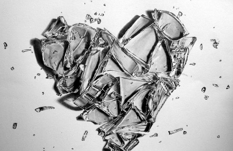 A heart made out of glass and broken into several pieces.