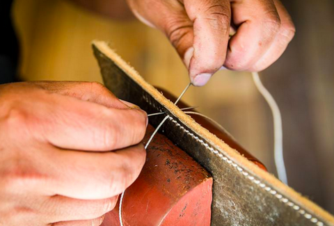 Hands sewing two pieces of leather together.