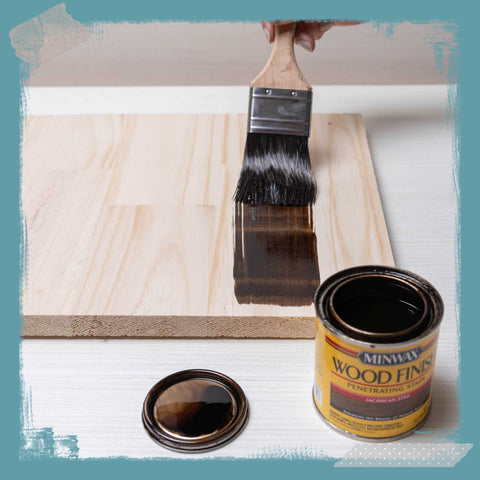 Paintbrush applying stain to wood.