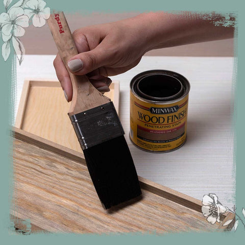 Hand painting wood with a paintbrush.