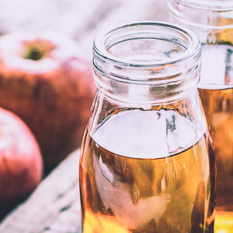 Clear bottle filled with apple cider vinegar on a table with apples nearby.