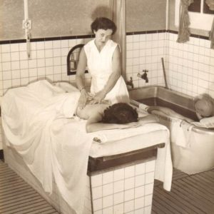 A woman gives another woman a massage in a treatment room.