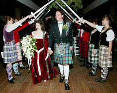 A bridal procession featuring kilts and a red celtic knot trimmed wedding dress