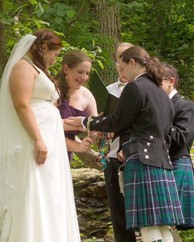 A bridesmaid ties one of the cords during a handfasting