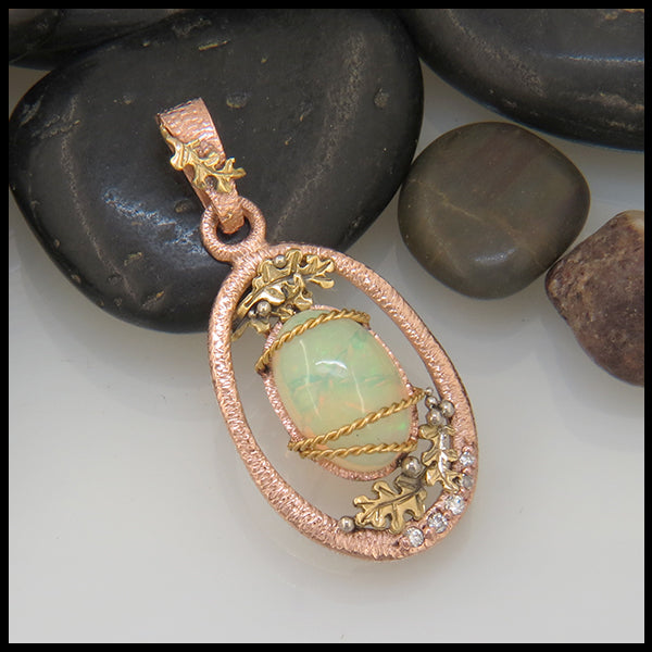 14k oval rose gold pendant with 18k yellow gold oak leaves and 5 accent diamonds framing an oval opal cabochon