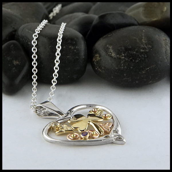 Profile view of silver heart pendant with chain