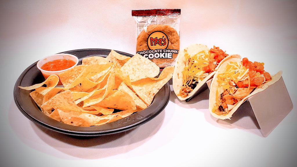 A serving includes Grilled Chicken, Shredded Cheese, Salsa, Black Beans, Rice, Sour Cream, Chips & a Cookie.