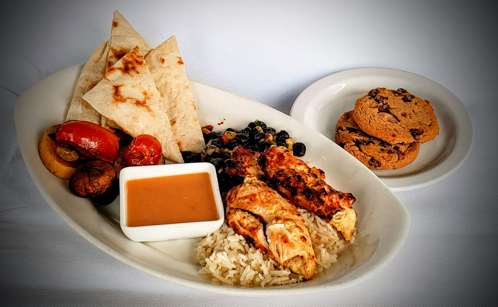 A serving includes All Natural Chicken, Spicy Mango Sauce, Homemade Flatbread, Grilled Vegetables, Black Bean + Corn Salad, Basmati Rice & a Chocolate Chip Cookie.