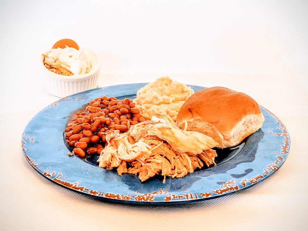 A serving includes Pulled Chicken, Baked Beans, Mashed Potatoes, Roll & Banana Pudding. Barbeque Sauce not pictured.