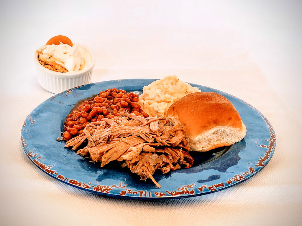 A serving includes Pulled Pork, Baked Beans, Mashed Potatoes, Roll & Banana Pudding. Barbeque Sauce not pictured.