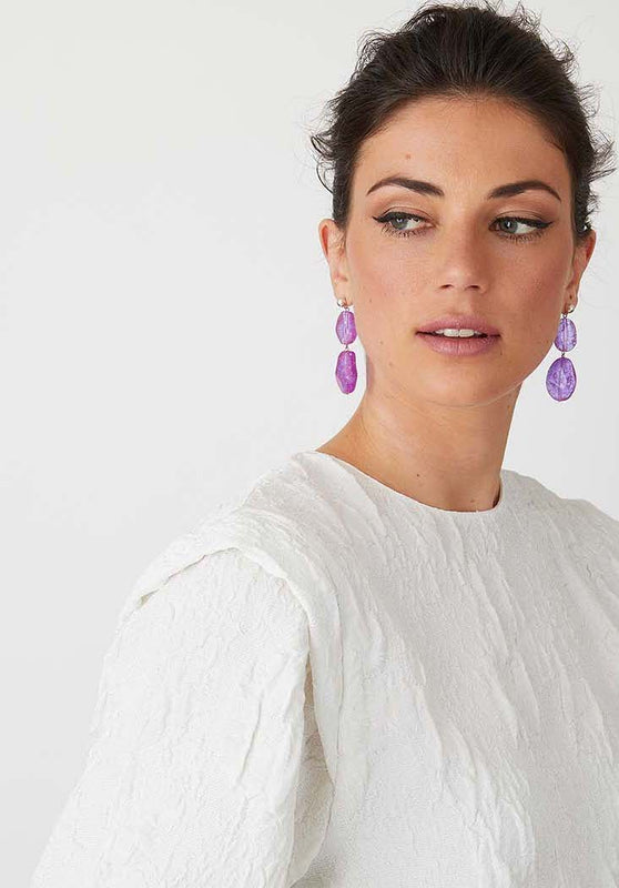 Purple resin statement earrings worn by a model in a white top