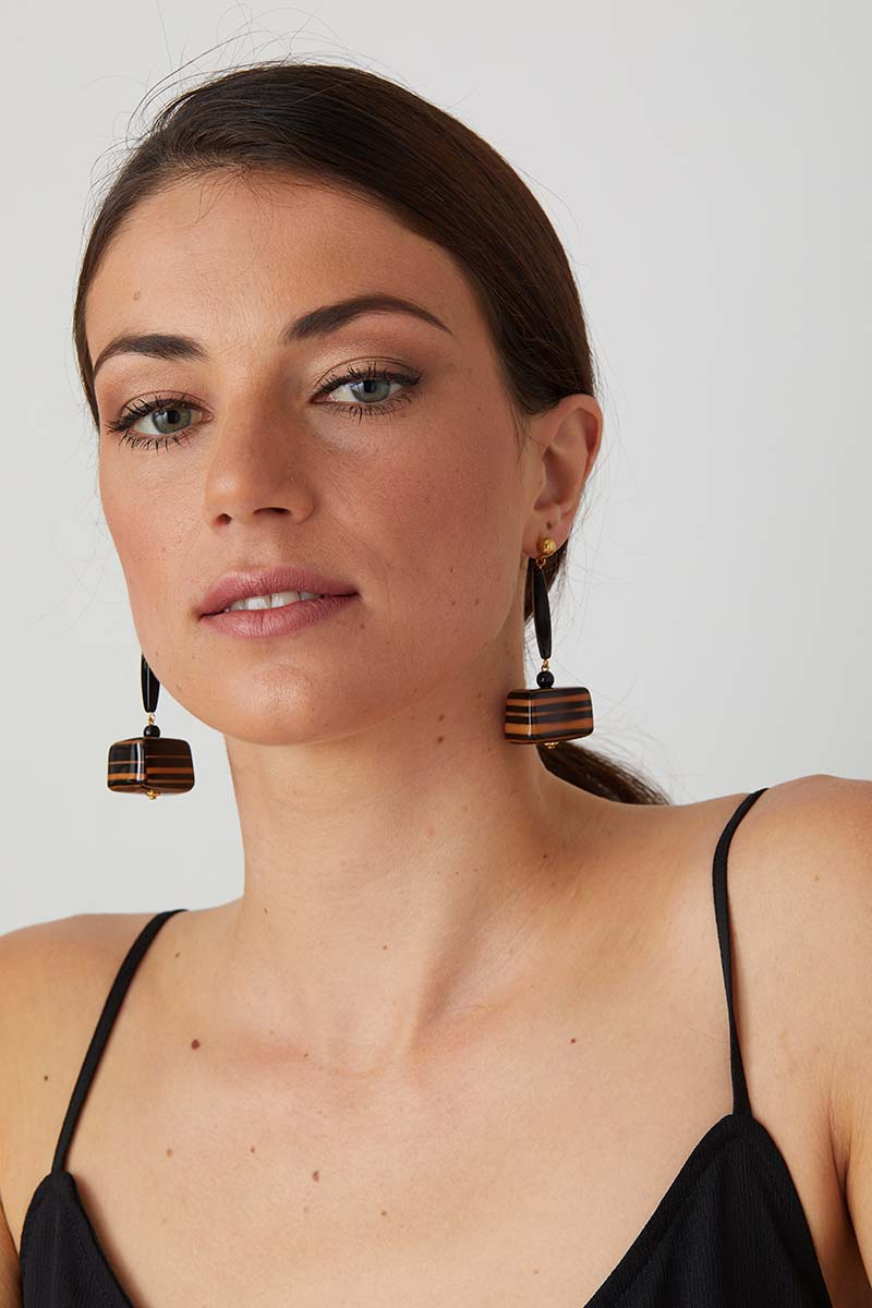 a pair of luxury italian orange and black striped statement earrings made of resin with a hand lacquered finish worn by a model in a black dress