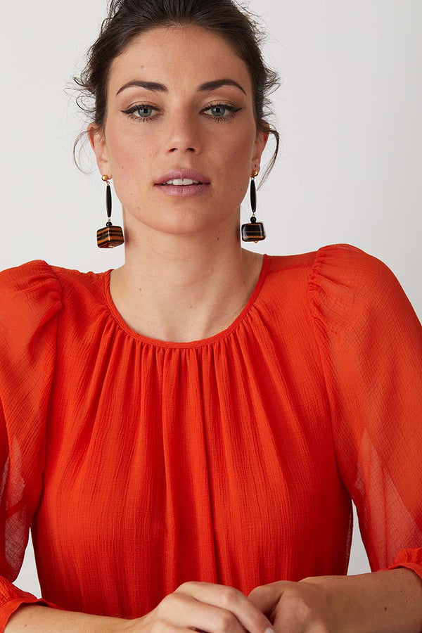 Black orange striped statement earrings worn by a model in a red dress