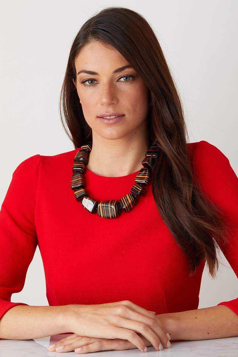 a luxury italian orange and black striped statement necklace made of resin with a hand lacquered finish worn by a model in a red dress